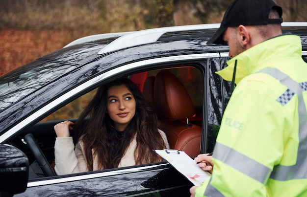 Agent de police masculin en uniforme vert avec bloc-notes vérifiant le véhicule sur la route.