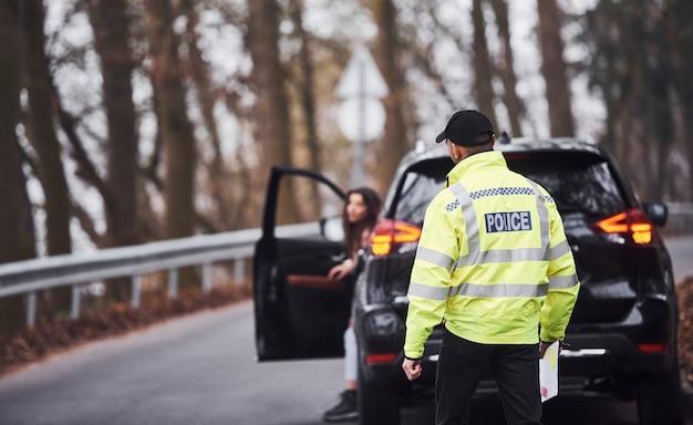 Agent de police masculin en uniforme vert marchant vers le véhicule sur la route.
