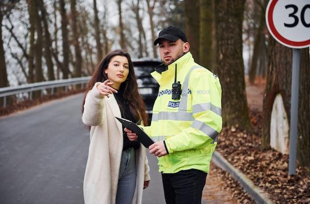 Agent de police masculin en uniforme vert parlant avec la propriétaire de la voiture sur la route.