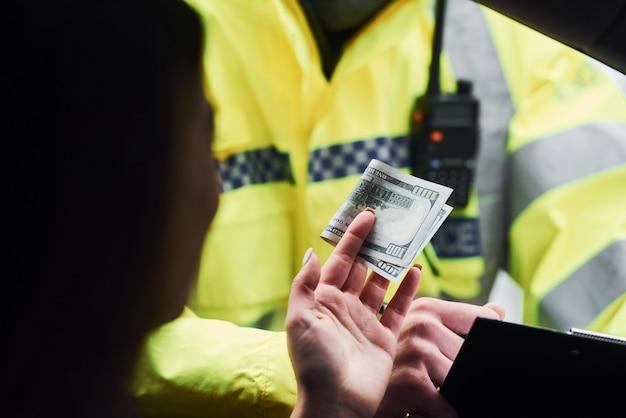 Agent de police masculin en uniforme vert vérifiant le véhicule sur la route. femme essayant de donner un pot-de-vin.