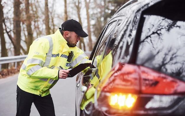 Agent de police masculin en uniforme vert vérifiant le véhicule sur la route.