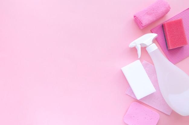 Agent de produits de nettoyage, éponges, serviettes et gants en caoutchouc, fond rose.