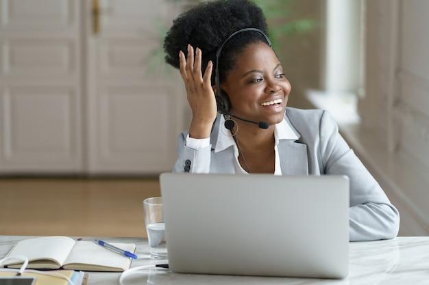 Agent répartiteur femme noire portant un casque avec microphone parler avec le client à la fenêtre