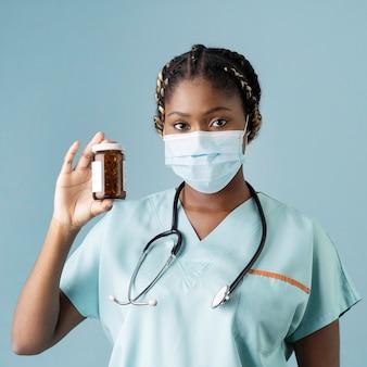 Agent de santé coup moyen tenant un contenant de pilules