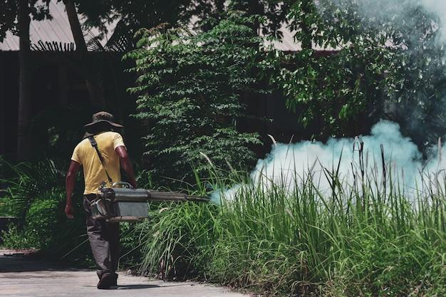 Agent de santé fumigant le jardin