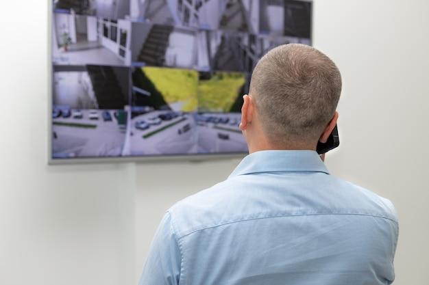 Agent de sécurité debout devant un grand moniteur de vidéosurveillance et parlant au téléphone portable