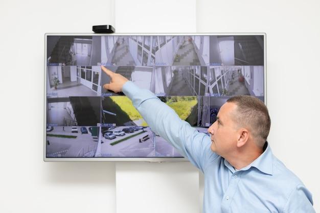 Agent de sécurité debout devant un grand moniteur de vidéosurveillance système de sécurité de surveillance