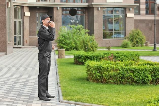 Agent de sécurité masculin avec radio portable, à l'extérieur
