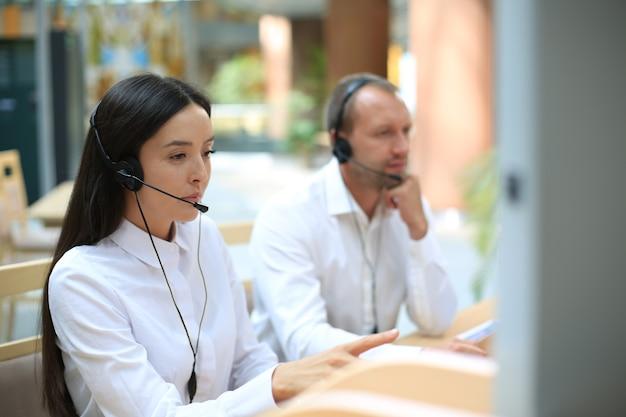 Agent de service amical parlant au client dans le centre d'appels