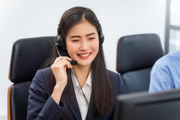 Agent de service client femme asiatique avec des casques travaillant sur ordinateur