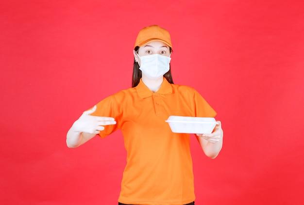 Agent de service féminin en code vestimentaire de couleur orange et masque tenant un emballage de nourriture à emporter