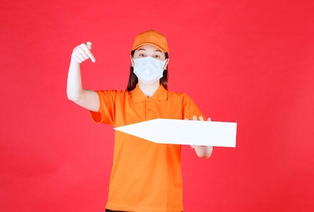 Agent de service féminin en code vestimentaire de couleur orange et masque tenant une flèche pointant vers la gauche