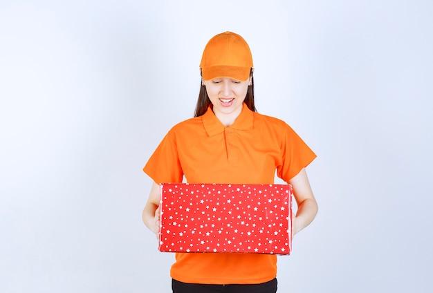 Agent de service féminin en code vestimentaire de couleur orange tenant une boîte-cadeau rouge.