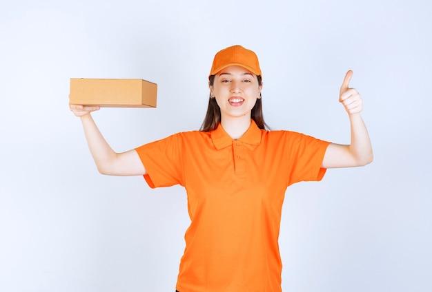 Agent de service féminin en code vestimentaire de couleur orange tenant une boîte en carton et montrant un signe de main réussi