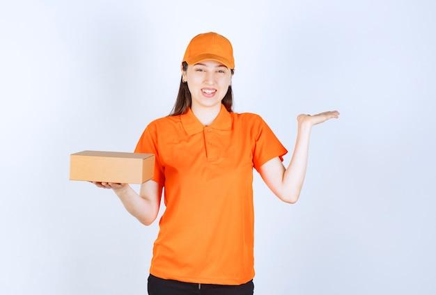 Agent de service féminin en code vestimentaire de couleur orange tenant une boîte en carton