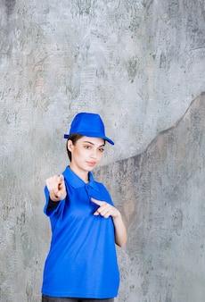 Agent de service féminin en uniforme bleu montrant la personne devant.