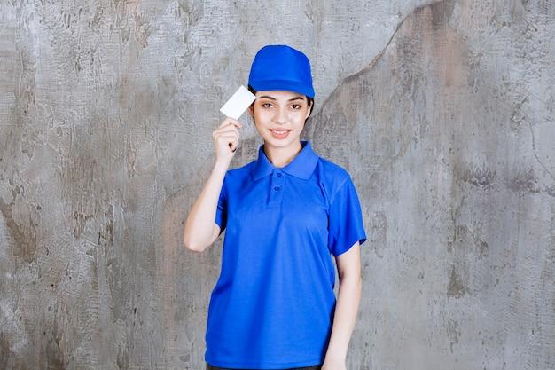 Agent de service féminin en uniforme bleu présentant sa carte de visite et semble confus ou réfléchi.