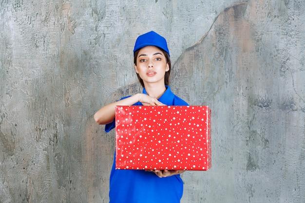 Agent de service féminin en uniforme bleu tenant une boîte-cadeau rouge avec des points blancs dessus.