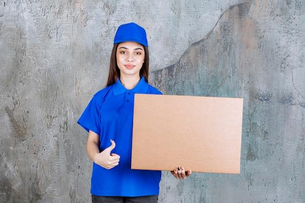 Agent de service féminin en uniforme bleu tenant une boîte en carton et montrant un signe de main positif.