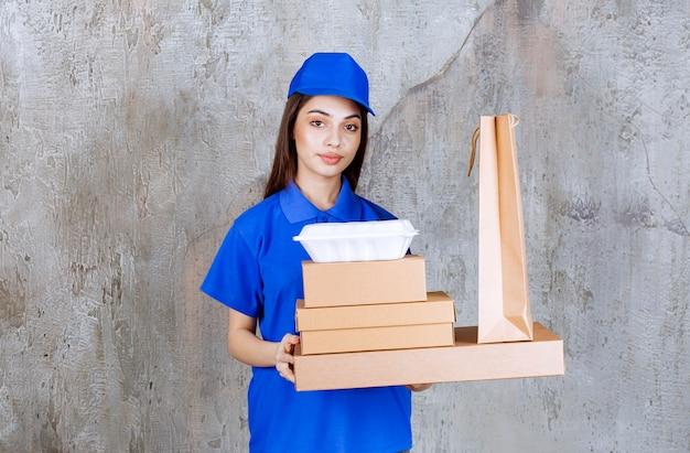 Agent de service féminin en uniforme bleu tenant des boîtes en carton, des paniers et des boîtes à emporter