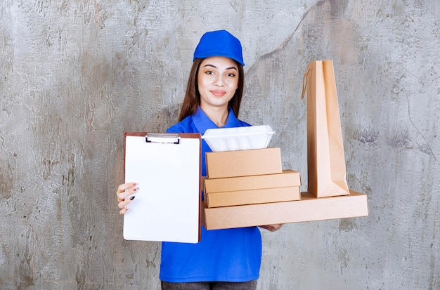 Agent de service féminin en uniforme bleu tenant des boîtes en carton, des sacs et des boîtes à emporter et présentant la liste des signatures.