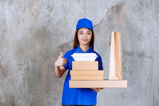 Agent de service féminin en uniforme bleu tenant des boîtes en carton, shopping bax et boîtes à emporter tout en montrant un signe de main positif.