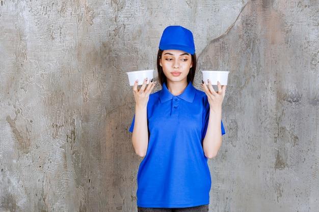 Agent de service féminin en uniforme bleu tenant deux gobelets en plastique.