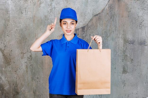 Agent de service féminin en uniforme bleu tenant un sac à provisions en carton et pensant avoir une idée.