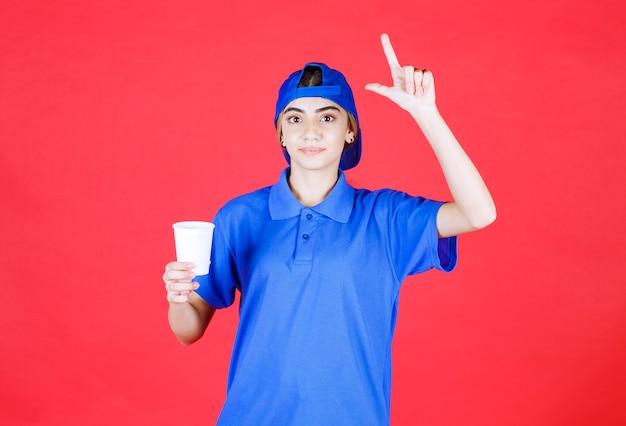 Agent de service féminin en uniforme bleu tenant une tasse de boisson jetable et ayant une bonne idée.