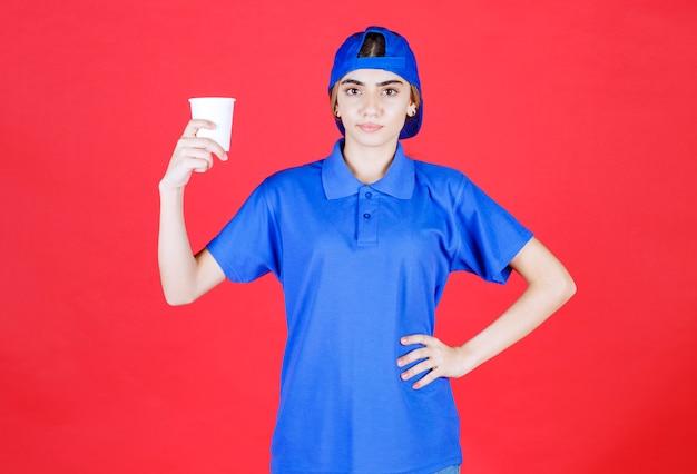 Agent de service féminin en uniforme bleu tenant une tasse de boisson jetable.