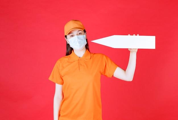 Agent de service féminin en uniforme de couleur orange et masque tenant une flèche pointant vers la gauche.