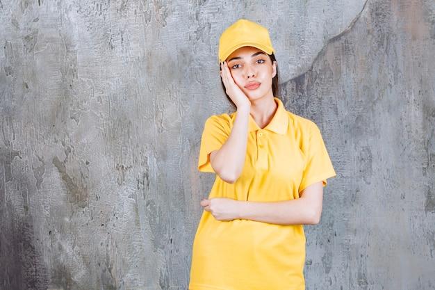 Agent de service féminin en uniforme jaune debout sur un mur de béton et a l'air confus et attentionné.