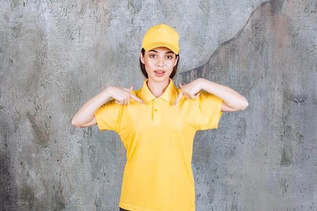 Agent de service féminin en uniforme jaune debout sur un mur de béton et se montrant.
