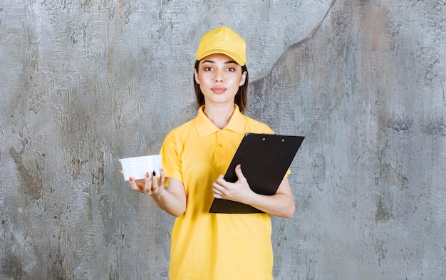 Agent de service féminin en uniforme jaune tenant un bol à emporter en plastique et un carnet d'adresses noir.