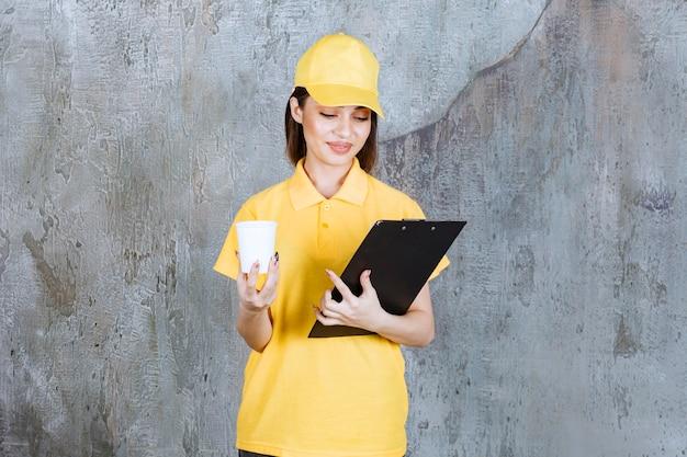 Agent de service féminin en uniforme jaune tenant un gobelet en plastique et un dossier d'adresses noir.