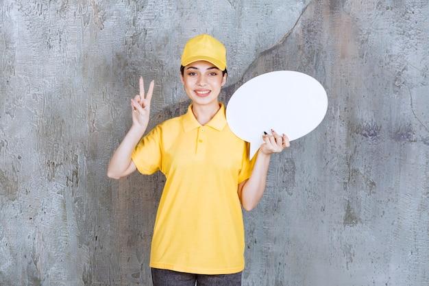 Agent de service féminin en uniforme jaune tenant un panneau d'information ovale et montrant un signe positif de la main.