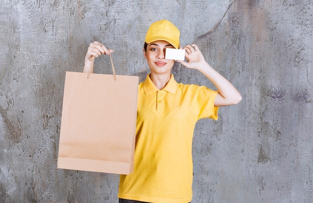 Agent de service féminin en uniforme jaune tenant un sac à provisions et présentant sa carte de visite.