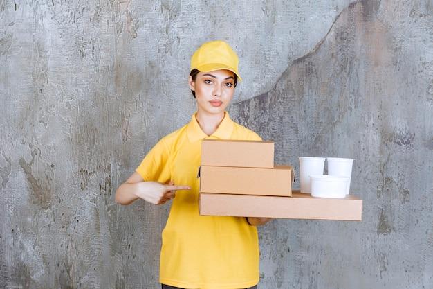 Agent de service féminin en uniforme jaune tenant un stock de boîtes en carton à emporter et de gobelets en plastique