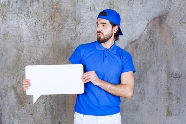 Agent de service masculin en uniforme bleu tenant un panneau d'information rectangulaire.
