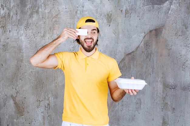 Agent de service en uniforme jaune tenant une boîte de nourriture à emporter en plastique et présentant une carte de visite.