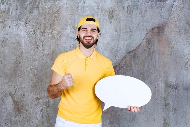 Agent de service en uniforme jaune tenant un panneau d'information ovale et montrant un signe positif de la main.