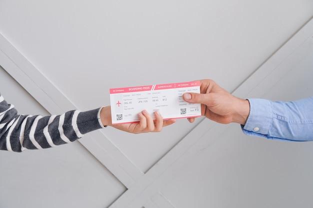 Agent de voyage donnant un billet client sur fond gris
