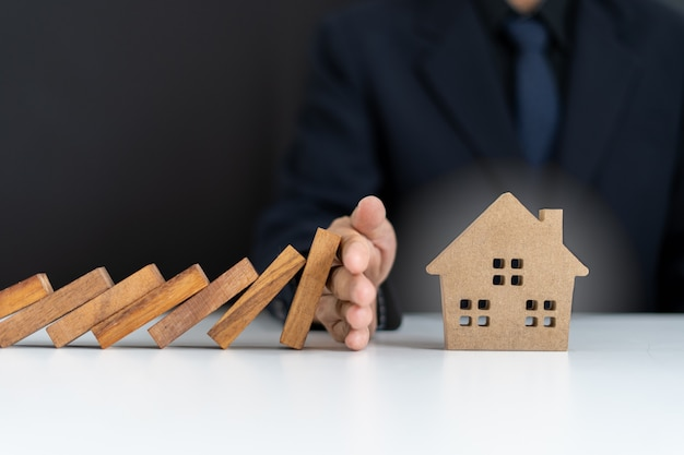Les agents d'assurance ou les chefs de famille utilisent leurs mains pour empêcher les dominos de tomber dans la maison. prévention des risques externes. régime d'assurance habitation