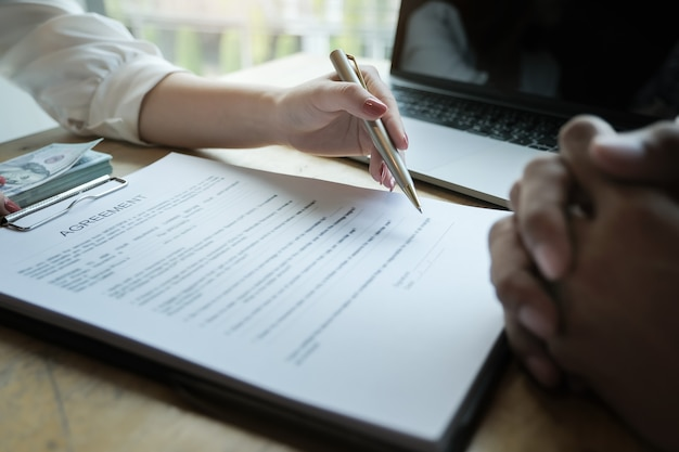 Des agents d'assurances discutant avec leurs clients de la signature d'un contrat d'achat d'assurance habitation. concepts d'accord.