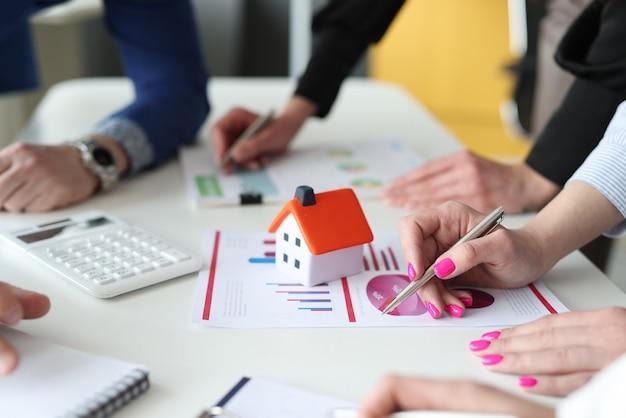 Agents commerciaux discutant des statistiques de vente immobilière en gros plan