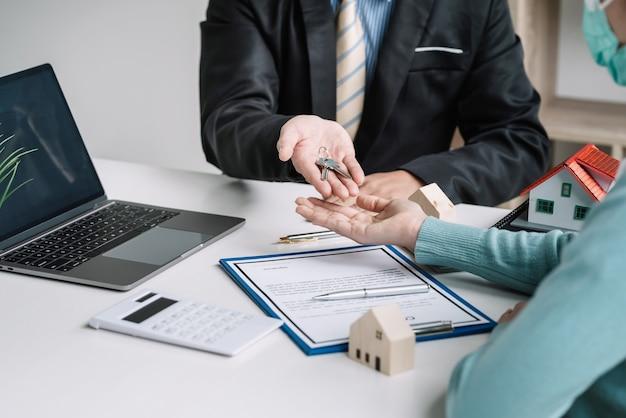 Les agents immobiliers livrent la clé de la maison aux clients pour échanger des documents contractuels de réussite au bureau