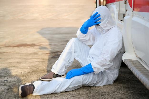 Agents de santé travaillant sur des ambulances d'urgence portant des vêtements de protection epi. les assistants médicaux sont assis tristes et fatigués dans l'ambulance.