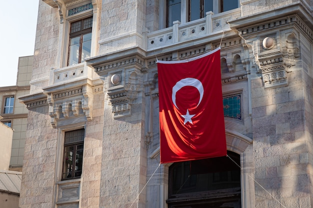 Agitant le drapeau national turc sur l'ancien mur de pierre