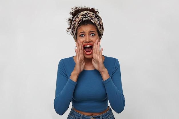 Agité jeune femme frisée aux cheveux noirs avec la peau foncée levant les mains à sa bouche tout en criant avec enthousiasme avec grande bouche ouverte, isolé sur fond blanc