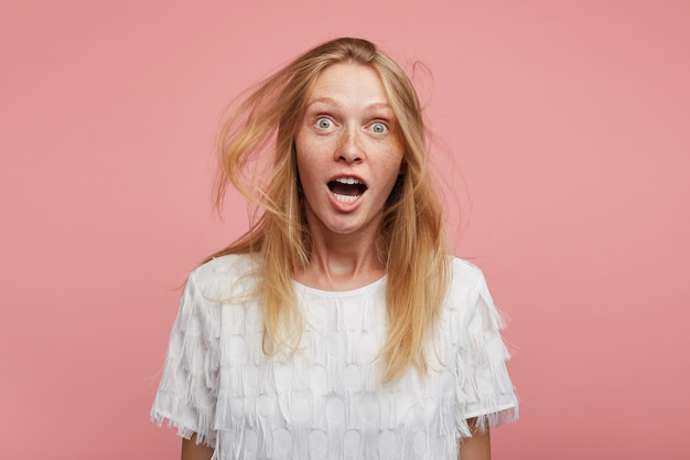 Agité jeune femme jolie rousse aux cheveux sauvages à la caméra avec enthousiasme avec de grands yeux ouverts, soulevant les sourcils avec surprise tout en posant sur fond rose